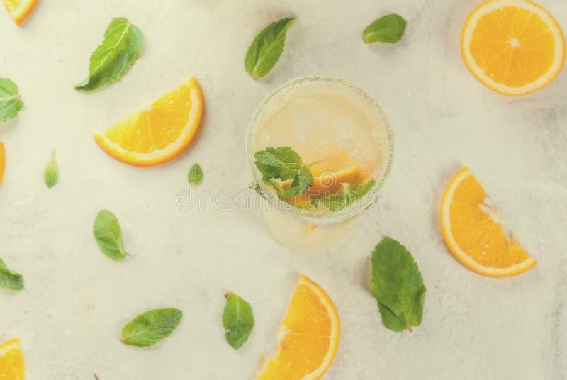 Orange und Carafe mit Zitrusfruchteiswasser Frische orange und tadellose Limonade mit Eis in den Gläsern lizenzfreie stockfotos