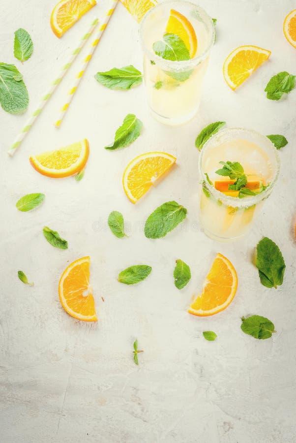 Orange und Carafe mit Zitrusfruchteiswasser Frische orange und tadellose Limonade mit Eis in den Gläsern lizenzfreies stockbild