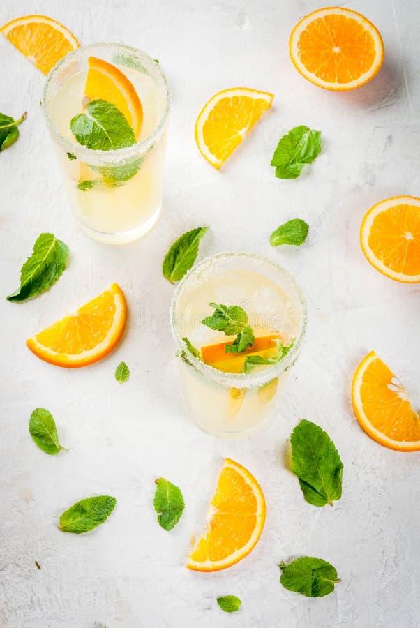 Orange und Carafe mit Zitrusfruchteiswasser Frische orange und tadellose Limonade mit Eis in den Gläsern stockbild
