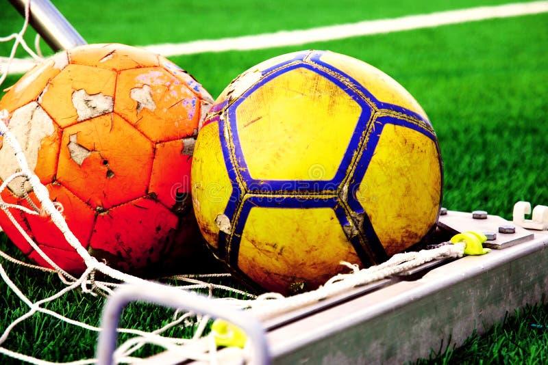 Orange und gelbe Fußbälle in der Ecke des Ziels gegen grünen Fußballplatz lizenzfreie stockfotografie