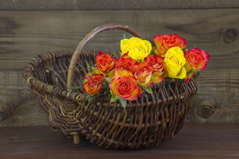 Orange und gelbe Rosen in einem Korb lizenzfreie stockbilder