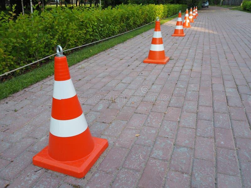 Orange und weiße gestreifte Verkehrskegel zusammen angekettet stockfoto