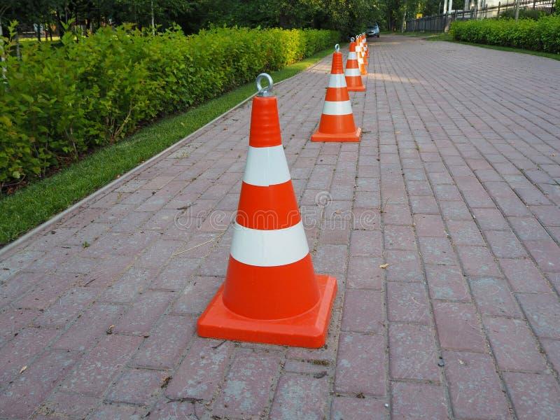 Orange und weiße gestreifte Verkehrskegel zusammen angekettet lizenzfreies stockfoto