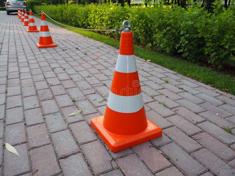Orange und weiße gestreifte Verkehrskegel zusammen angekettet lizenzfreie stockfotos