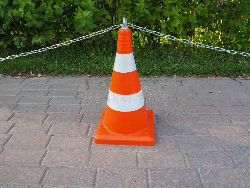 Orange und weißer gestreifter Verkehrskegel mit einer Kette lizenzfreies stockbild