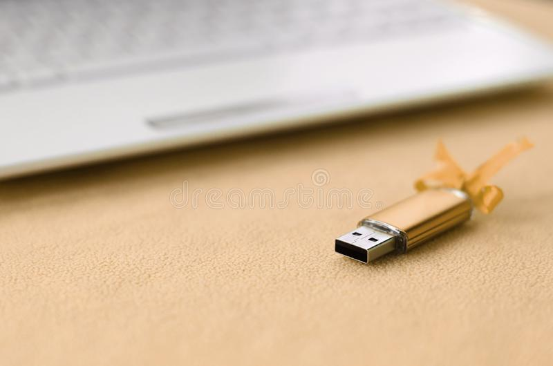 Orange usb flash memory card with a bow lies on a blanket of soft and furry light orange fleece fabric beside to a white laptop. Classic female gift design for stock photo