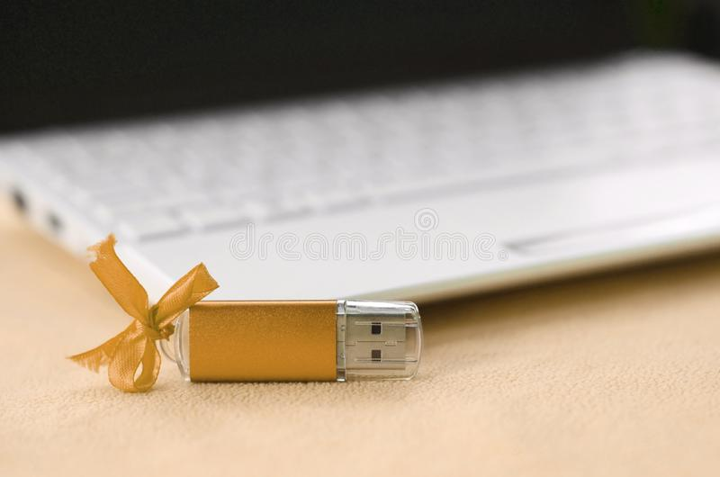 Orange usb flash memory card with a bow lies on a blanket of soft and furry light orange fleece fabric beside to a white laptop. Classic female gift design for stock image