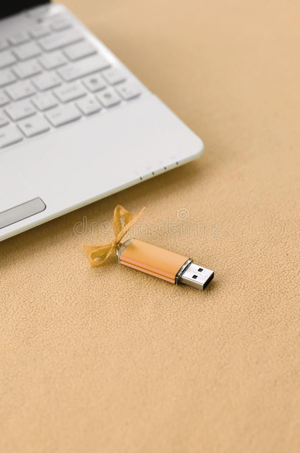 Orange usb flash memory card with a bow lies on a blanket of soft and furry light orange fleece fabric beside to a white laptop. Classic female gift design for stock images