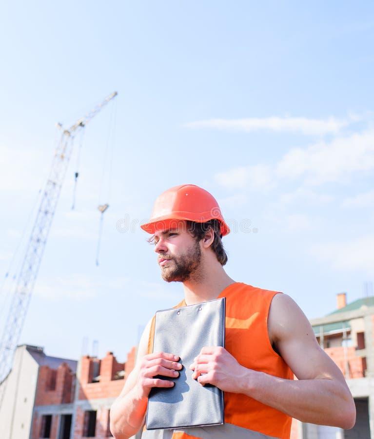 Orange väst- och hjälmarbeten för byggmästare på konstruktionsplatsen Leverantörkontroll enligt plan Skyddande hjälm för grabb royaltyfri fotografi