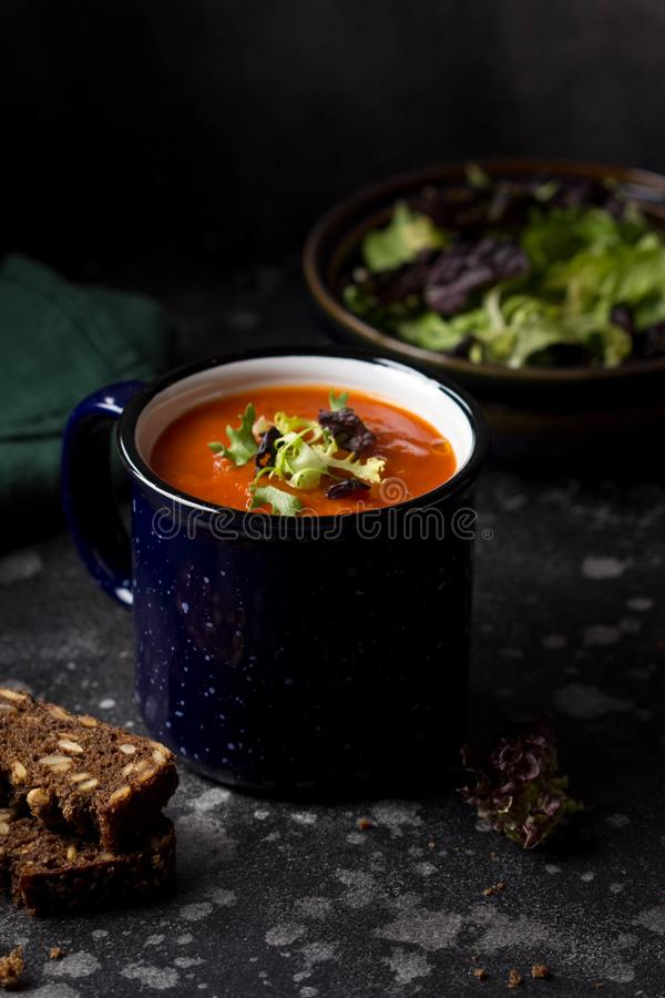 Orange vegetable cream soup in mug (tomato, carrot, lentil, pumpkin), delicious hot homemade lunch in cup. Dark background stock photo