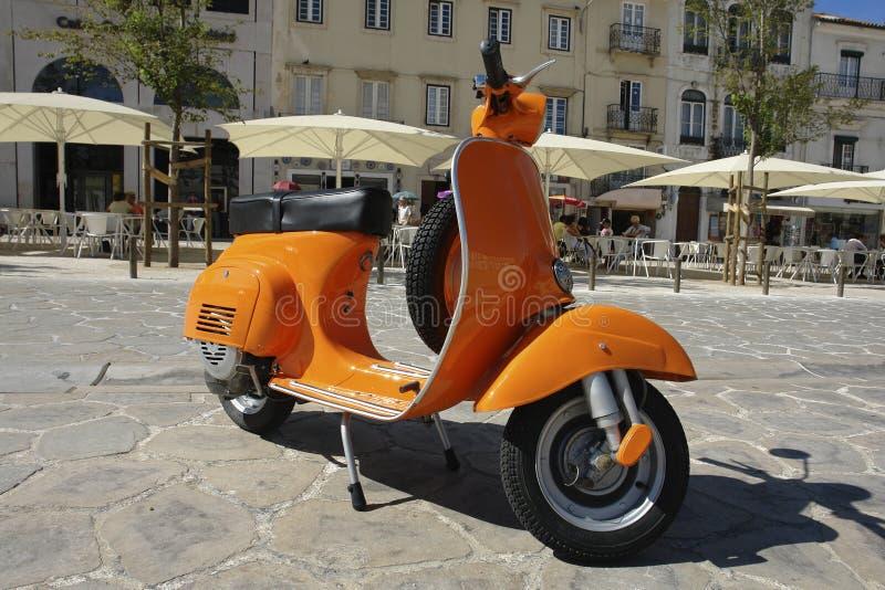 Orange Vespa. Parked on the sidewalk