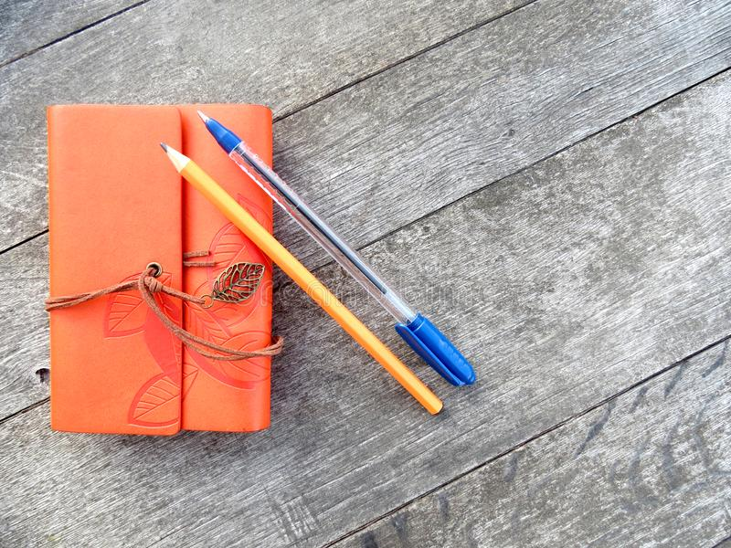 Orange vintage notebook with pen and pencil on wooden table. Creative writing concept. Flat lay top view. Vintage style. Orange vintage style notebook with pen stock images