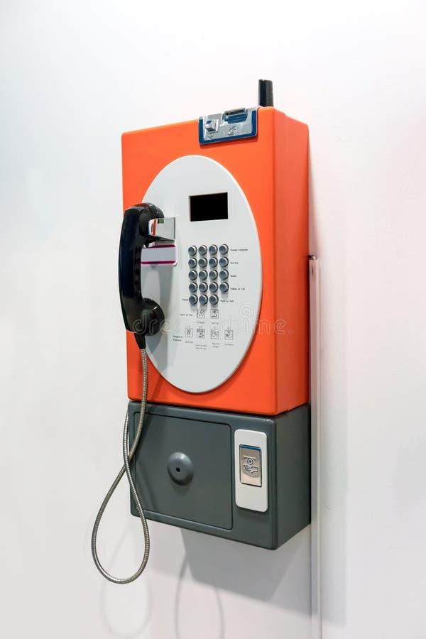 Orange vintage public pay phone stock photos