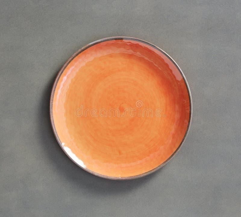 Orange virvelMelamineplatta med mörkt - grå bakgrund royaltyfria bilder