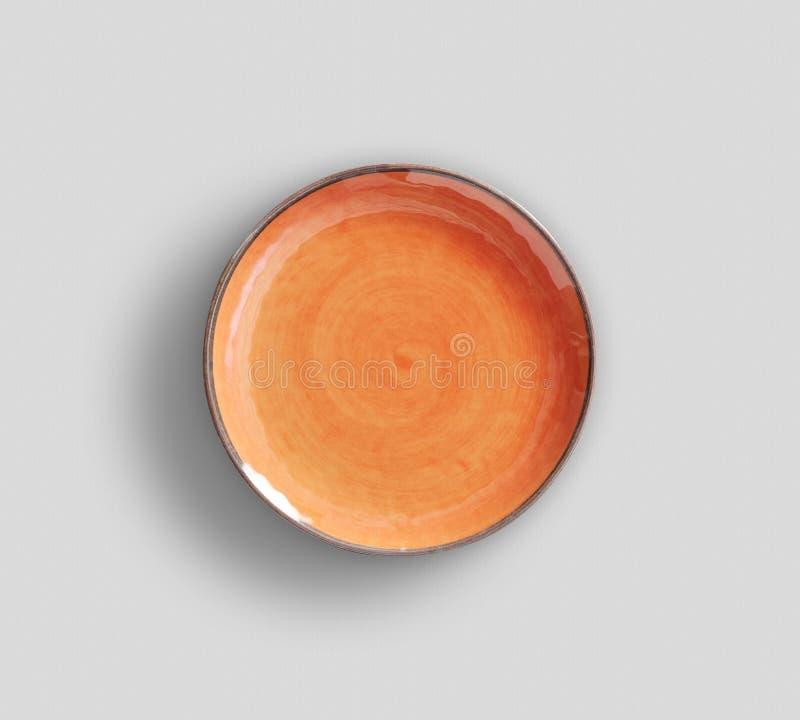 Orange virvelMelamineplatta med m?rkt - gr? bakgrund royaltyfri fotografi
