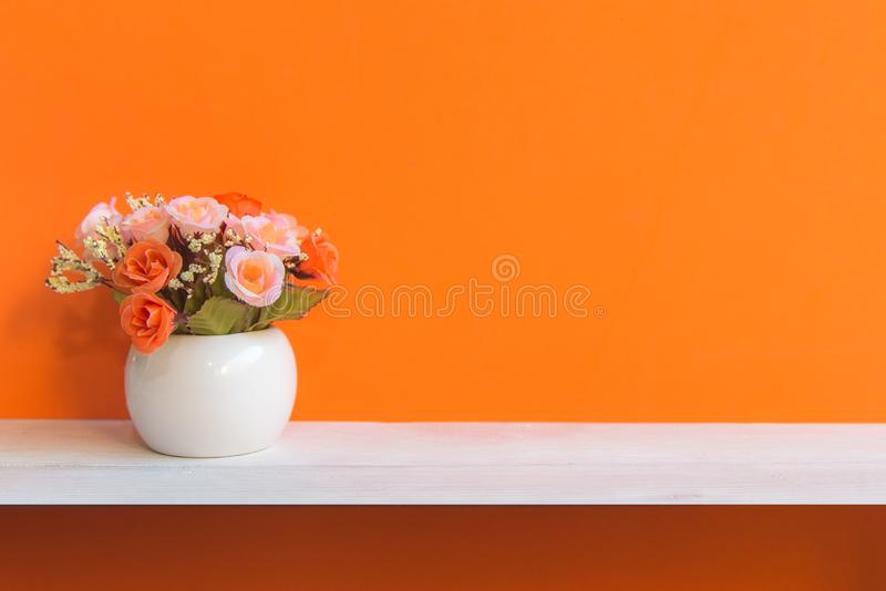 Orange wall with flowers on shelf white wood, copy space for text. Still life Concept stock photo