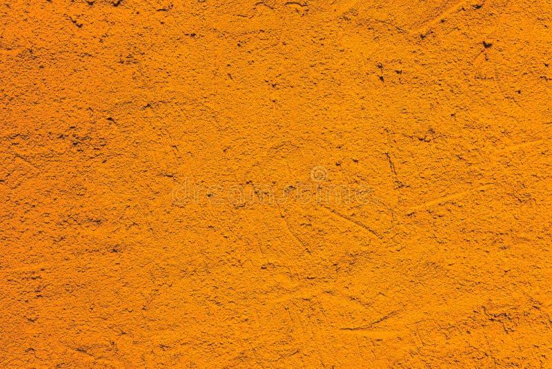Orange wall from a house coarse exterior facade with intense vivid color as an empty rustic texture backgruond. Orange wall from a house coarse exterior facade stock photo