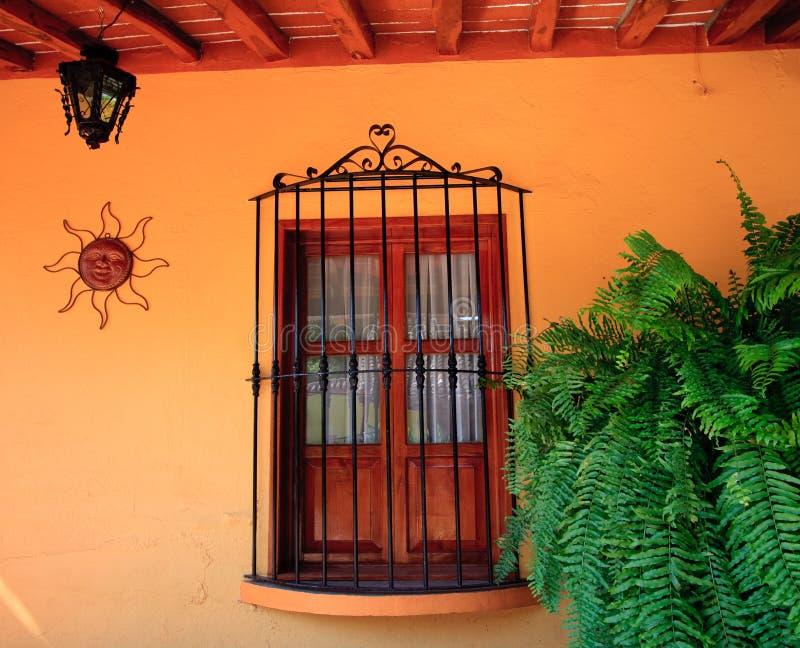 Orange Wand mit hölzernem Fenster lizenzfreie stockfotos