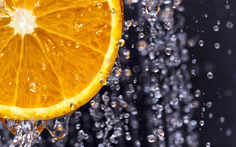 Orange among water droplets royalty free stock photo