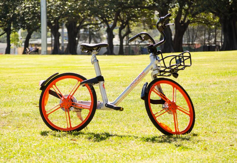 Orange wheels bicycle `Mobike bike sharing` is dockless system uses a smartphone app to unlock bicycles, charging an hourly rate. SYDNEY, AUSTRALIA. – On stock photos