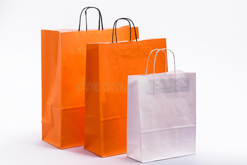 Orange and white paper bag with handles for shopping stock image