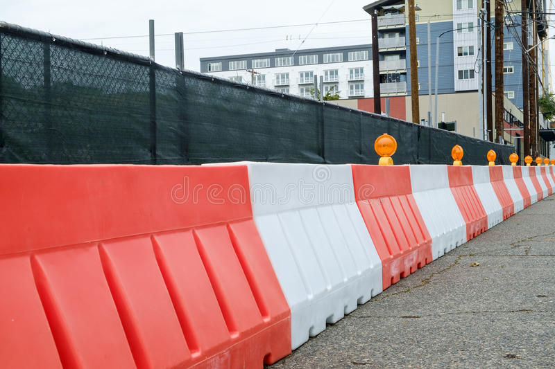 Orange and white plastic jersey barriers protect a