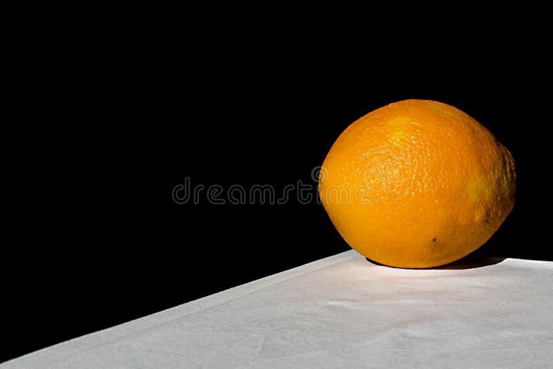Orange on white table with black background stock photos