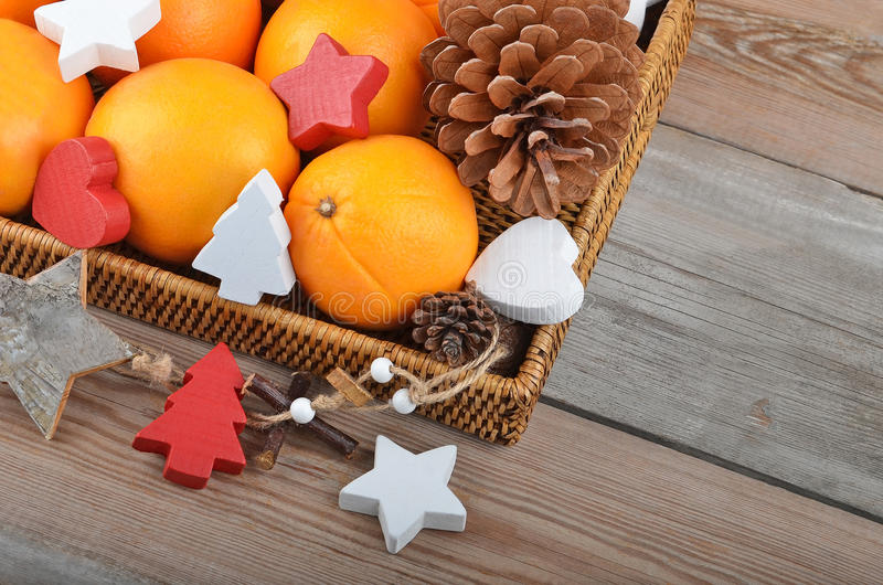 Orange in wickered tray with Christmas decor. Orange in wickered tray on wooden background with Christmas decor stock image