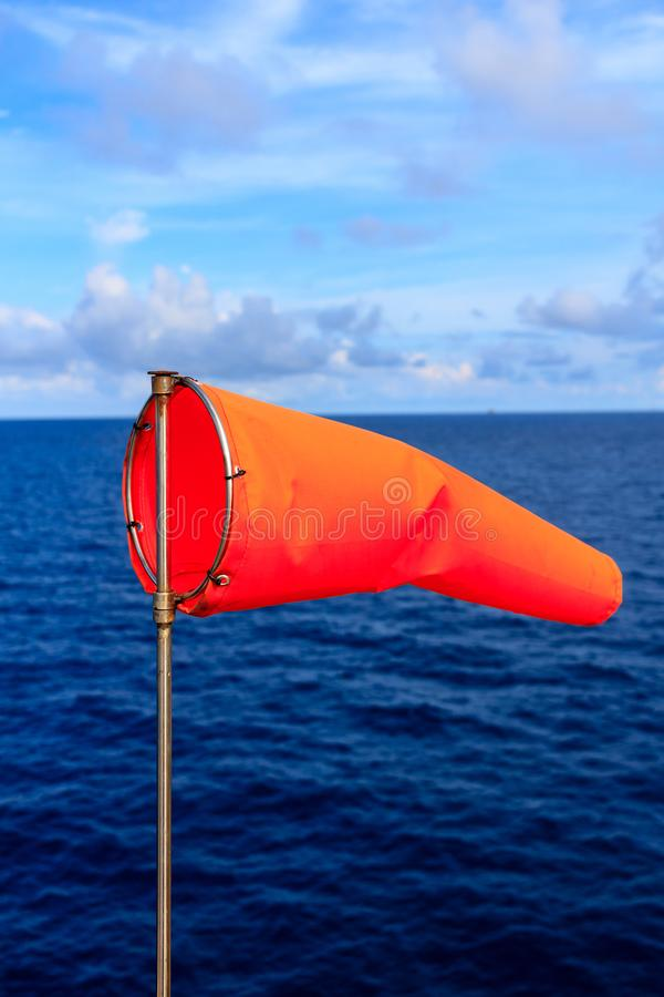 Orange wind sock in blue sky and blue sea with white cloud background. royalty free stock image