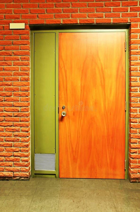 Orange wooden door and bricks royalty free stock photography