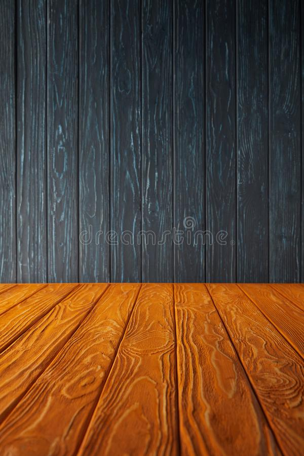 Orange wooden table and dark blue. Wooden wall royalty free stock photos