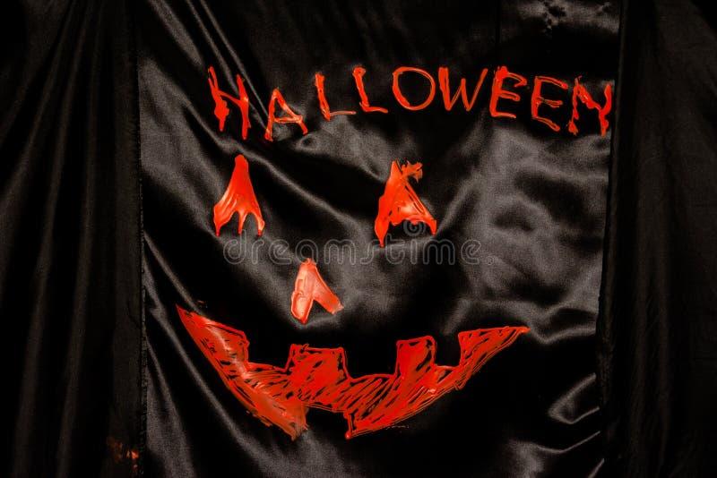 Orange word spelling Halloween on black cloth stock photography