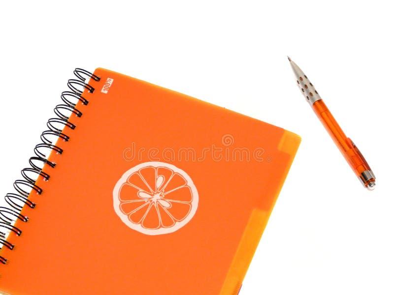 Orange writting-book. Orange writing-book with orange pen isolated on white royalty free stock photography