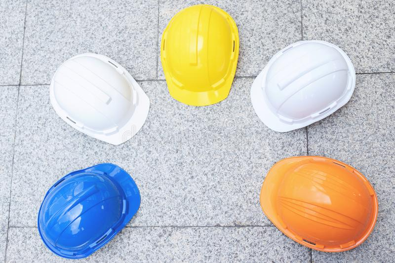 Orange, yellow, blue, white hard safety wear helmet hat in the project at construction site building on concrete floor. On city. helmet for workman as engineer stock photos