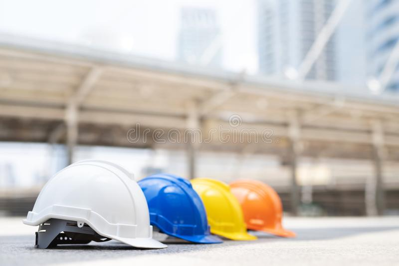 Orange, yellow, blue and white hard safety wear helmet hat in the project at construction site building on concrete floor. On city. helmet for workman as royalty free stock photos
