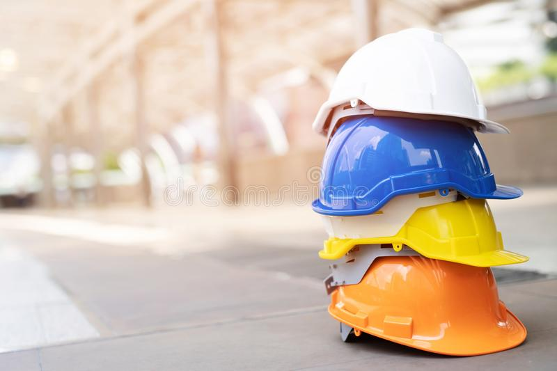 Orange, yellow, blue and white hard safety wear helmet hat in the project at construction site building on concrete floor on city. Helmet for workman as royalty free stock photo