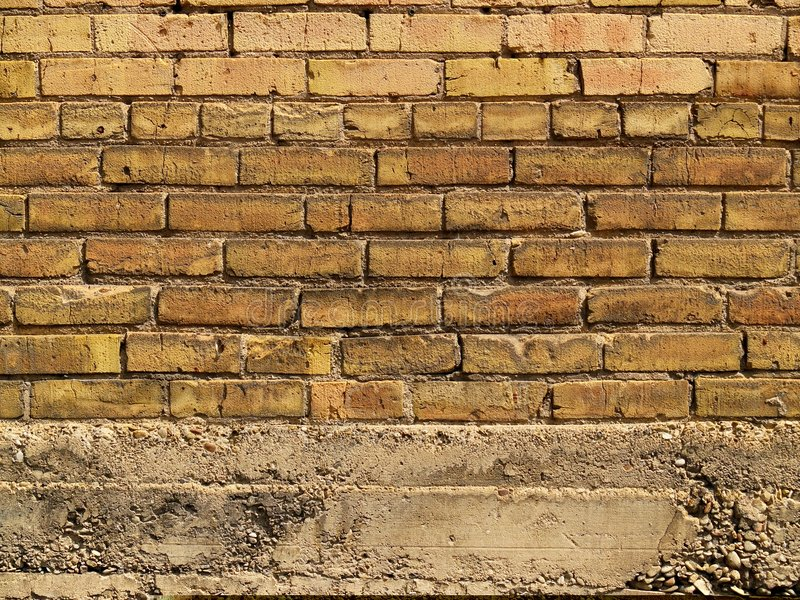 Orange and yellow brick wall over concrete stock photography