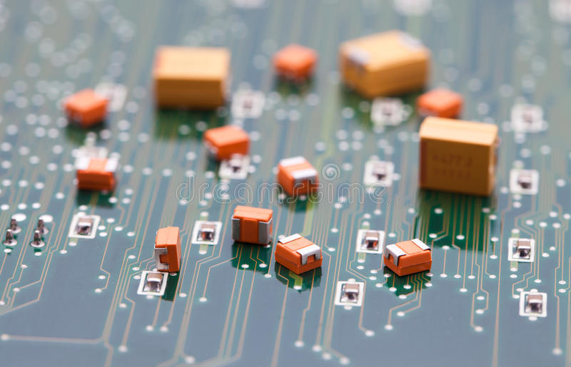Orange and Yellow capacitor on green pcb.  stock photos