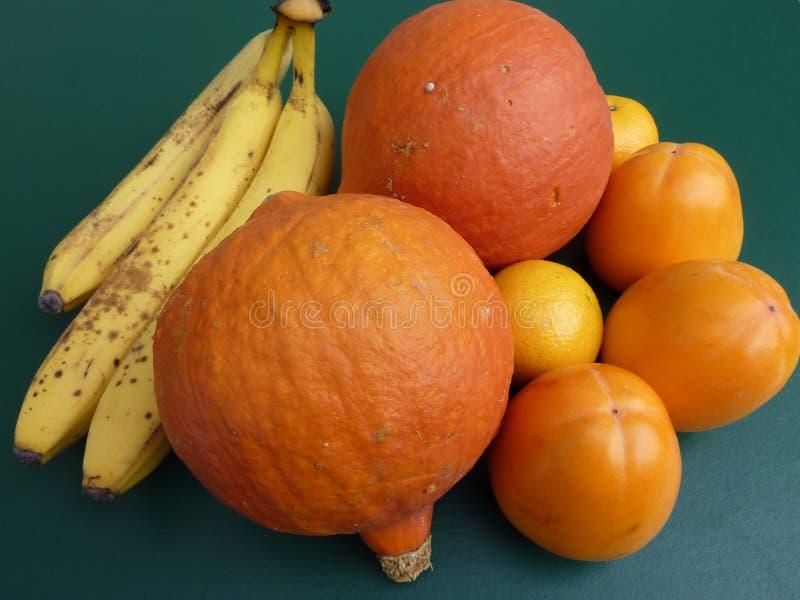 Orange and yellow fruit. Bananas, pumpkins, tangerines and persimmon fruit royalty free stock image