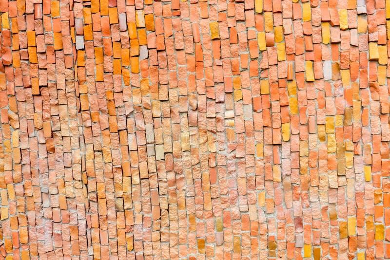 Orange yttersida av den gamla smula abstrakta dekorativa mosaiken som bakgrund Mångfärgade keramiska stenar på väggbyggnad fotografering för bildbyråer