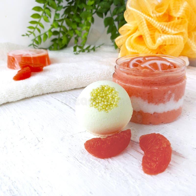 Orange Zucker scheuert sich mit Badekurortbombe und -tangerine auf weißem hölzernem Hintergrund lizenzfreie stockfotografie