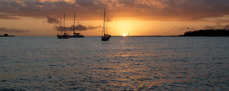 Orangefarbener Sonnenaufgang-Meerblick mit Yachten am Anker australien stockbild