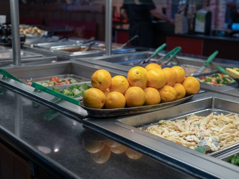 Orangen angehäuft auf einem Buffettisch mit verschiedenen Teigwaren lizenzfreies stockbild