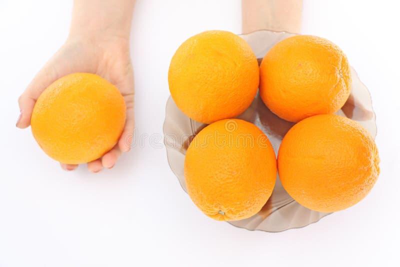 Orangen in einer Schüssel in der Hand lizenzfreie stockbilder