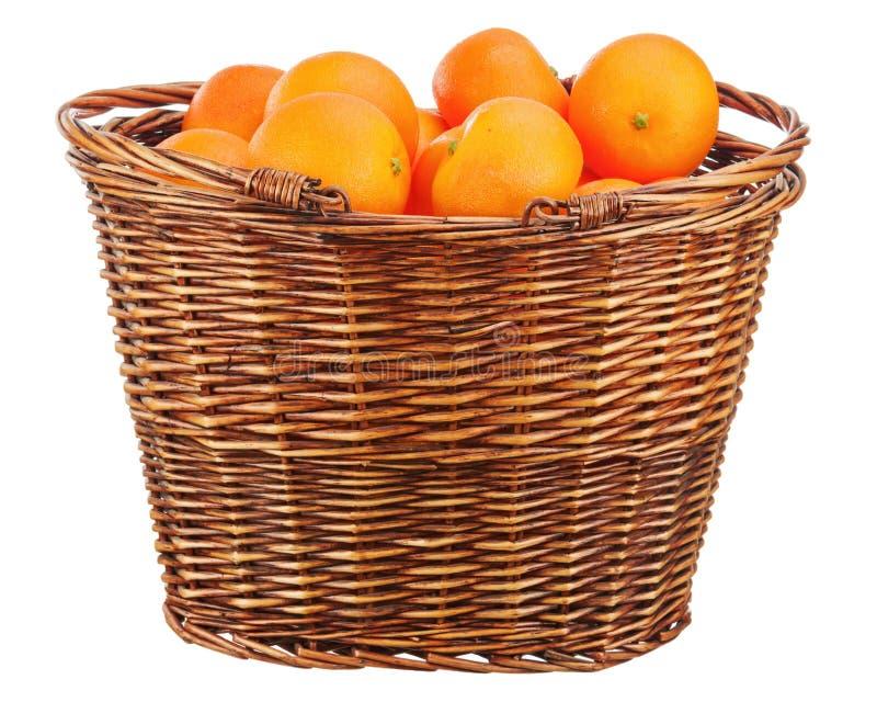 Orangen im Weidenkorb lokalisiert auf Weiß. stockbild