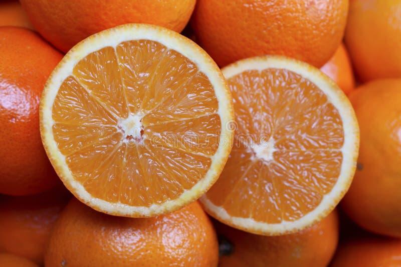 Orangen mit einem Schnitt zur Hälfte auf die Oberseite stockbilder