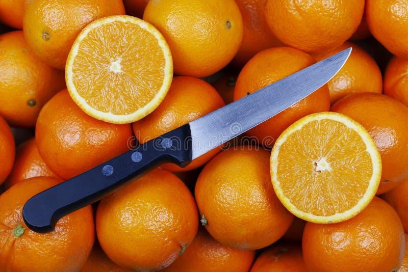 Orangen mit einem Schnitt zur Hälfte auf Spitze und einem Messer stockfoto