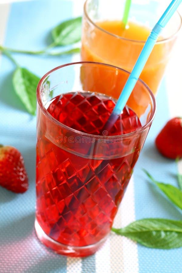 Orangen- und Erdbeeresaft lizenzfreies stockbild