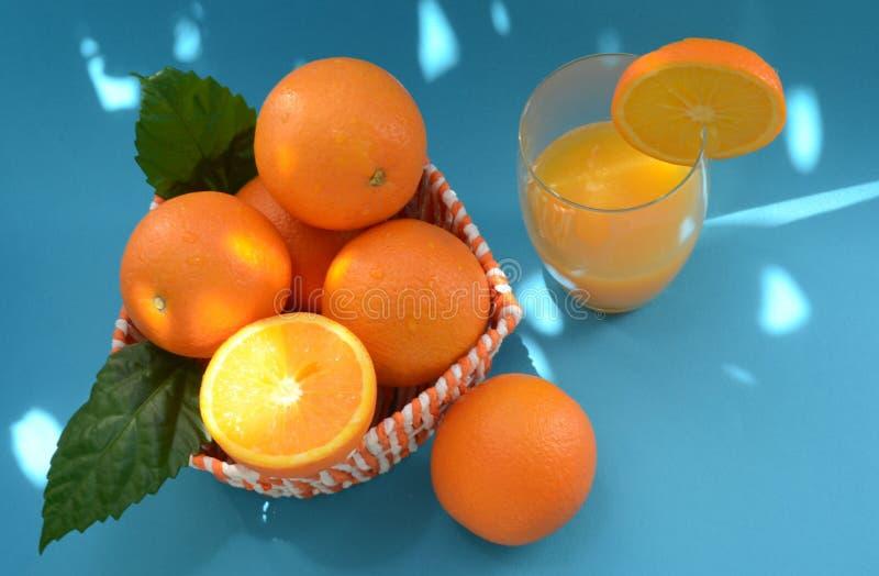 Orangen und frisch zusammengedrückter Orangensaft auf einem blauen Hintergrund mit Höhepunkten des hellen Sonnenscheins stockfotos