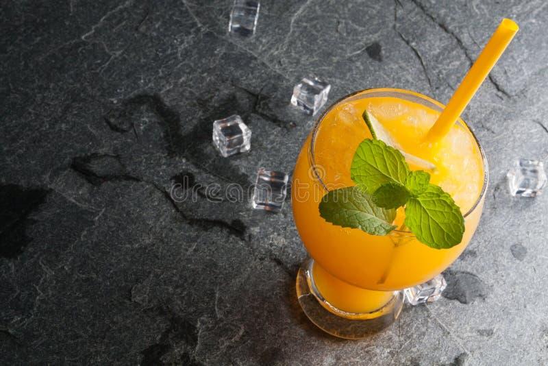 Orangen und Saft auf Steintischplatteansicht lizenzfreie stockbilder